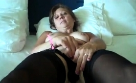 busty-mature-brunette-in-stockings-caresses-her-aching-pussy
